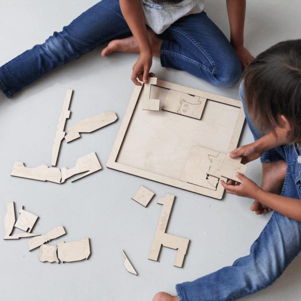Kinderen van 5 en 6 jaar aan het puzzelen met houten dieren